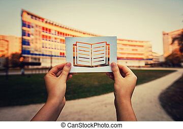 Hand holding a paper with books icon over university background. Lack of education global issue, students don't attend or are not enrolled in school. Inequality, marginalization and poverty problems.