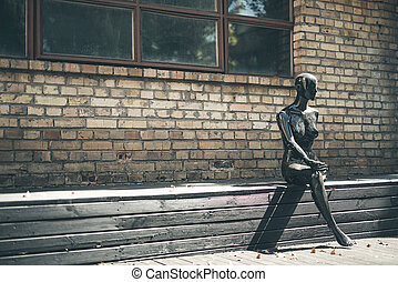 Laconic image of the mannequin sitting outdoors