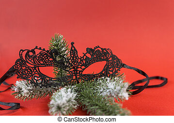 Lacy black mask on spruce branch on red background,