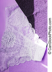 Lacy white sexy women's panties on purple neon background. Vertical shot, top view, flat lay
