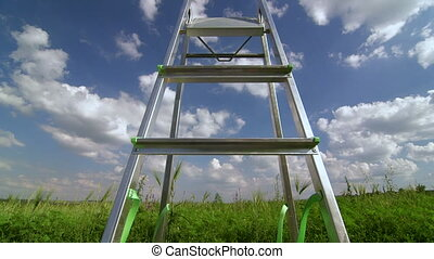 Ladder against blue sky with fluffy clouds - Ladder in green...