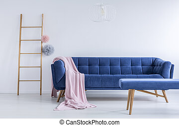 Ladder and navy blue sofa - Colorful balls on ladder next to...