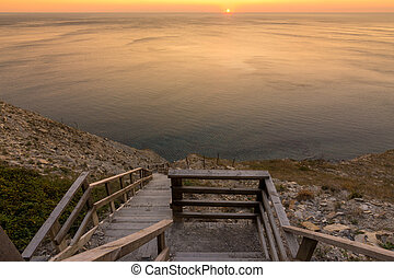 Ladder going down to the sea at sunset, Anapa, Russia