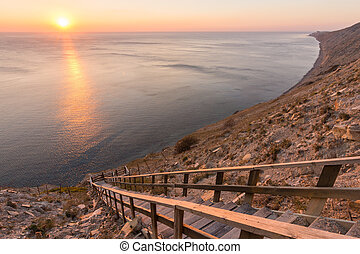 Ladder going down to the sea on a rocky cliff, sunset, Anapa, Russia