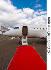 ladder in a private jet and red carpet on blue sky