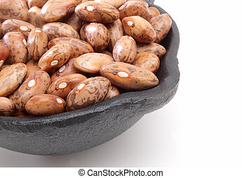 Close up of organic pinto beans in a cast iron laddle.