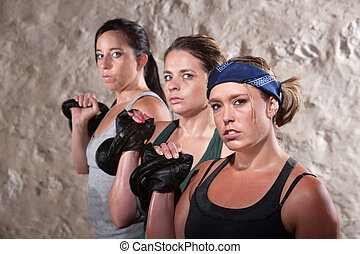 Ladies Lifting Weights in Boot Camp Workout - Three pretty...
