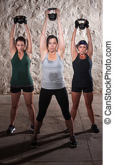 Three strong women lifting weights during boot camp workout