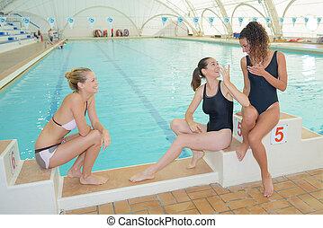 Ladies sat on swimming pool starting blocks