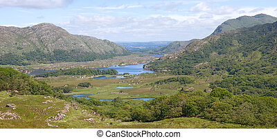 """The beautiful Lakes of Killarney, nestling among the Kerry mountains on a sunny summer day. This scenic view of the valley was taken from the vantage point called """"Ladies' View"""", named after Queen Victoria's ladies-in-waiting who visited here in 1861."""