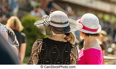 Ladies with hats on the race track. Romantic summer hats. Retro style summer romance.
