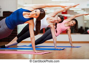 lado, tablón, actitud del yoga, por, tres mujeres