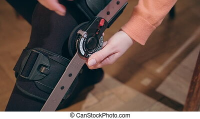 Lady Adjusting Supportive Leg Brace - Detail of the lower...