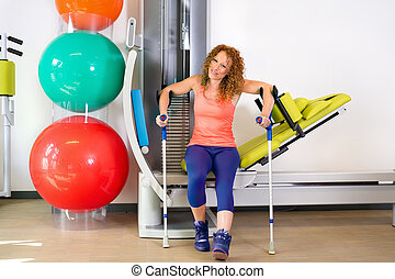 Lady at exercise machine with crutches