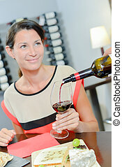 Lady being served a glass of red wine