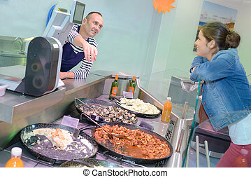 Lady being served at food counter