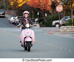 lady biker on pink scooter - youthful sixty year old woman...