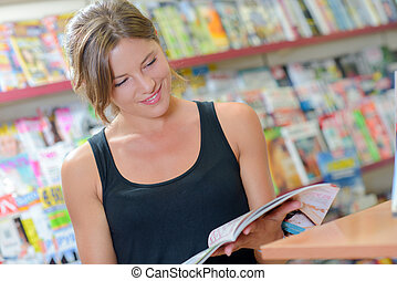 Lady browsing through magazine in newsagents