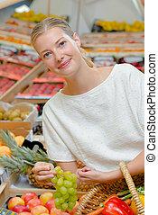 Lady choosing grapes