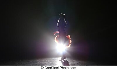 Lady dancing cha-cha-cha in the studio on a dark background, smoke, silhouette
