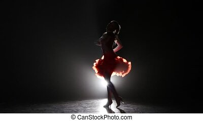 Lady dancing rumba in the studio on a dark background, smoke, silhouette