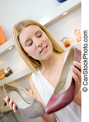Lady deliberating between two shoes