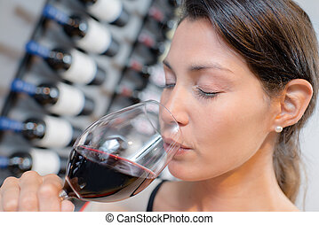 lady drinking glass of red wine, eyes closed