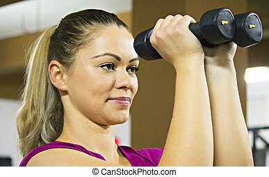 Lady fitness classes - Cute strong woman lifting weight in...