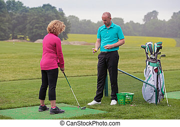 Lady golfer being taught by a golf pro. - A lady golfer...