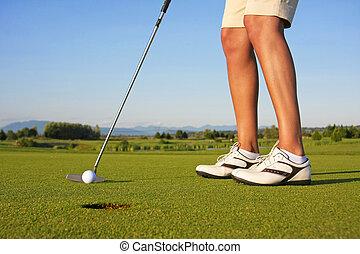Lady golfer putt - Close up of a lady golfer, putting.