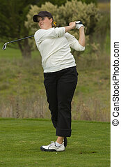 Lady golfer swinging club on tee box