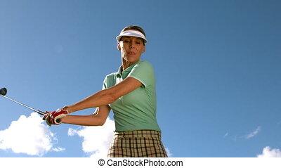Lady golfer swinging her club in slow motion