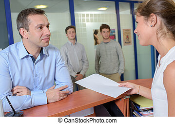Lady handing form to man at reception desk