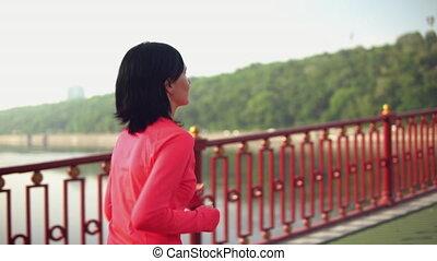 lady has a morning jog outdoors - brunette female runs fast...