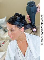 Lady having hair blow dried