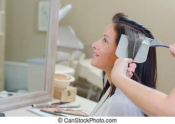 Lady having hair dyed