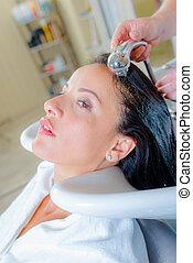 Lady having hair rinsed in salon