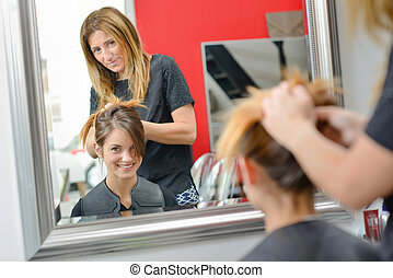 Lady having hair styled in hairdressers