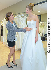 Lady having wedding dress fitted