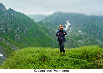 Lady hiker on a trail in the mountains