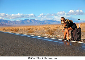 Lady hitchhiker - Young blonde girl sitting on suitcase on ...