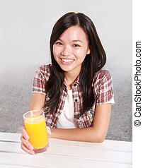 Lady holding a glass of orange juice