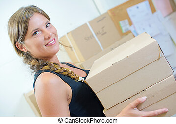 Lady holding a stack of boxes