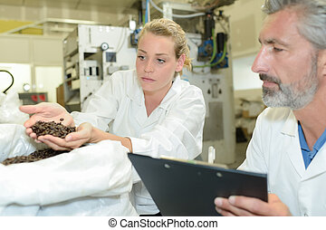 Lady holding handful of coffee beans being inspected by male colleague