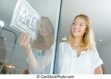 Lady holding open sign in shopfront