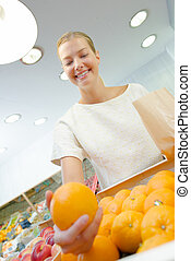 Lady holding orange in outstretched arm