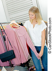 Lady holding top, stood next to rail of clothes