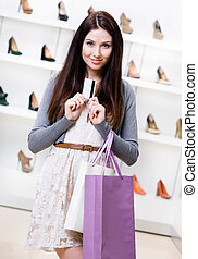 Lady holds credit card in footwear shop - Girl hands credit...