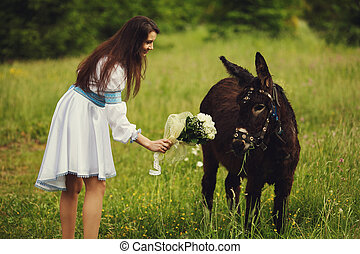 Lady in an embroidered dress stand on the field behind a donkey