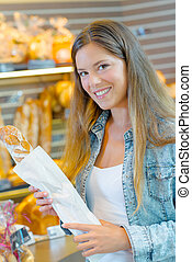 Lady in bakers holding a baguette